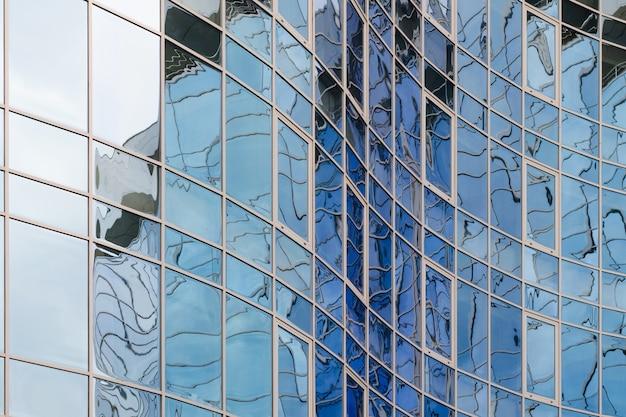 Powierzchnia szkła lustrzanego wieżowca odzwierciedlająca pochmurne niebo, kręta powierzchnia