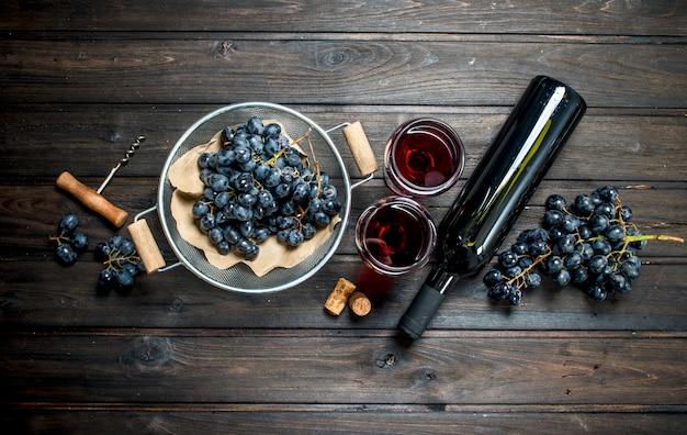 Powierzchnia wina. czerwone wino w okularach z winogronami. na drewnianej powierzchni.