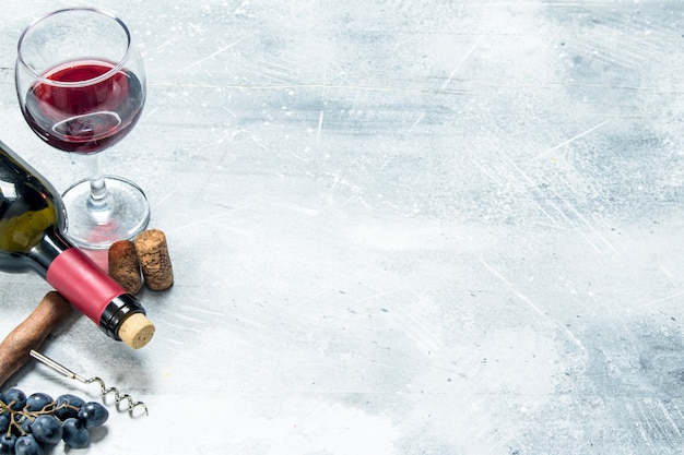 Powierzchnia wina. czerwone wino z winogronami i korkociągiem. na rustykalnej powierzchni.