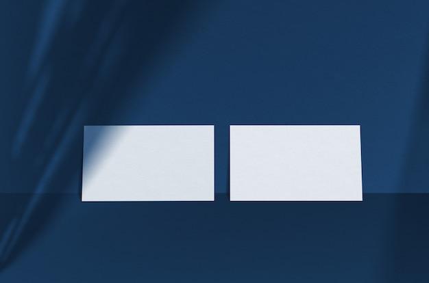 Powierzchnia wizytówki. naturalne oświetlenie nakładkowe rzuca cień na liście. wizytówki 3,5 x 2 cale. scena z cieni liści. klasyczny niebieski kolor. kolor roku 2020.