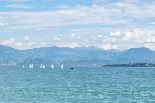 Powierzchnia wody jeziora z białymi żaglówkami i pasmem górskim na horyzoncie