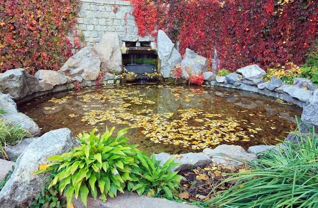 Powierzchnia wody stawu z odciętymi liśćmi i małym wodospadem w parku jesienią