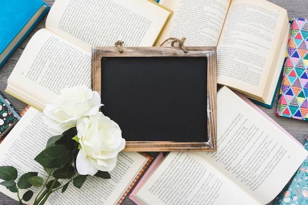 Powierzchnia z otwartymi książkami, łupkami i kwiatami