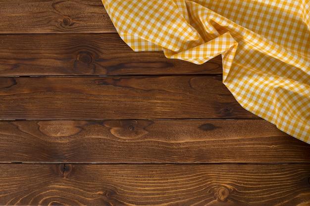 Powierzchnia z pustym drewnianym stołem z obrusem