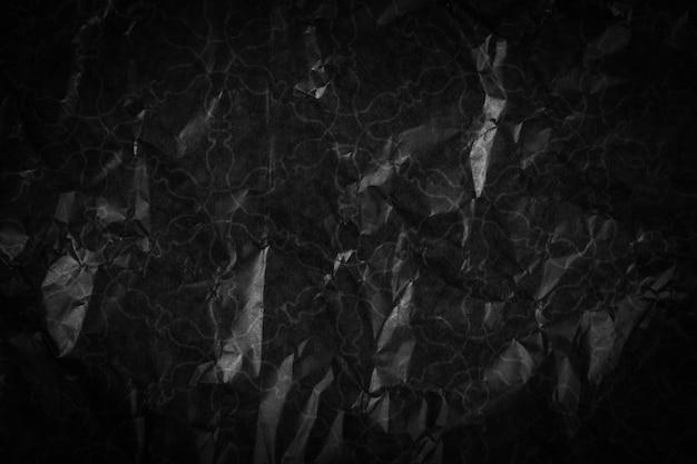 Powierzchnia z teksturą zmiętego czarnego papieru.
