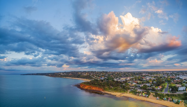 Powietrzna panorama wybrzeża, plaż i australijskiego obszaru podmiejskiego o zachodzie słońca z pięknymi chmurami. półwysep mornington, melbourne, victoria, australia.