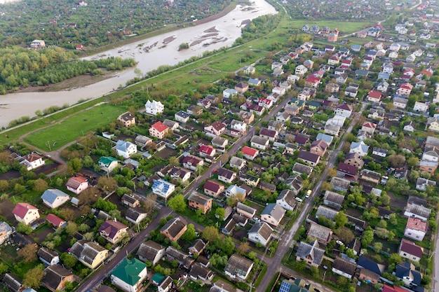 Powietrzny krajobraz małego miasteczka lub wioski z rzędami domów mieszkalnych i zielonymi drzewami.