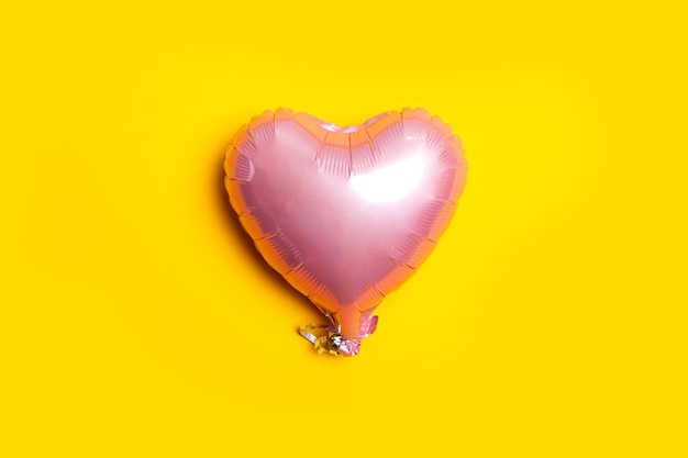 Powietrzny różowy metalowy balon w kształcie serca na jasnożółtym tle. widok płaski, widok z góry.