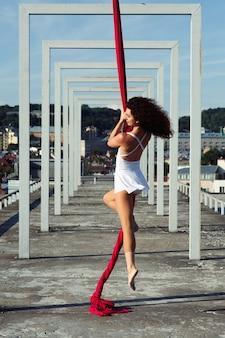 Powietrzny taniec na dachu, seksowna brunetka jedwabiu tancerz w białej sukni