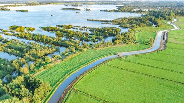 Powietrzny trutnia widok typowy holendera krajobraz z kanałami, polder wodą, zieleni polami i gospodarstwo rolne domami od above, holandia, holandie