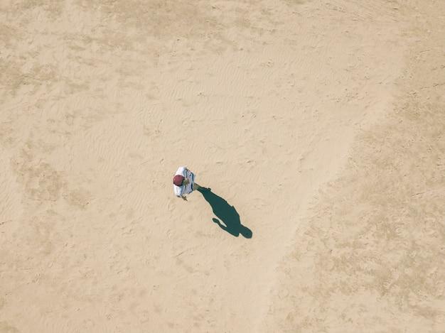 Powietrzny zasięrzutny widok chodzi samotnie w piaskowatej morze plaży młody człowiek, abstrakcjonistyczny pojęcia tło f