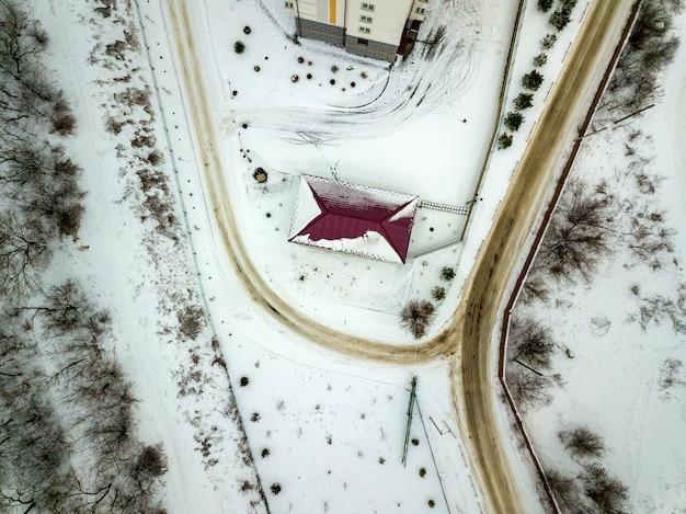 Powietrzny zima widok z góry dachu domu na ogrodzonej posesji, zaśnieżonym polu i brudnej drodze.
