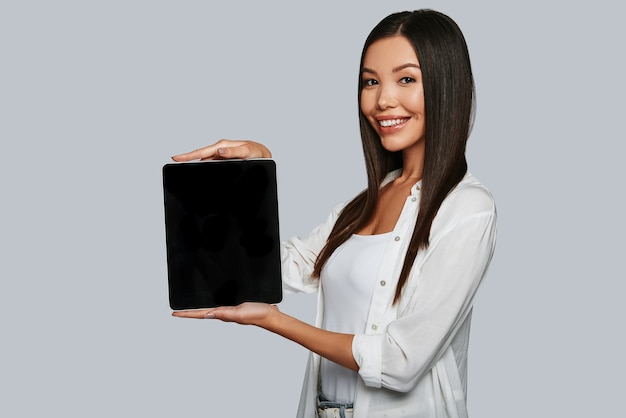 Powinieneś to zobaczyć. atrakcyjna młoda azjatka wskazuje miejsce na kopię na swoim cyfrowym tablecie i uśmiecha się, stojąc na szarym tle