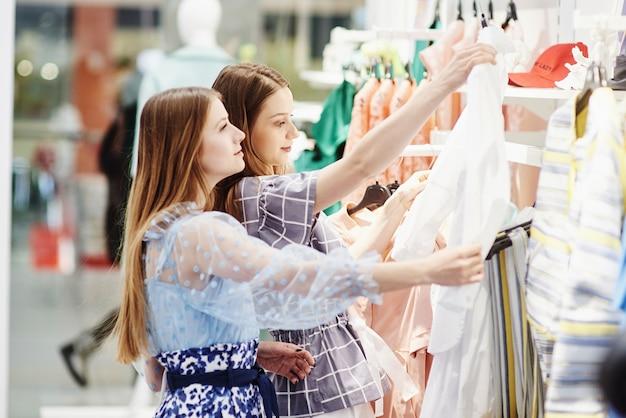 Powinniśmy spojrzeć na nowe sukienki. dwie piękne dziewczyny szukają w sklepie ubrań. dobry dzień na zakupy.