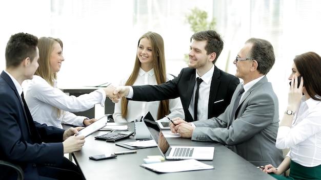Powitalny uścisk dłoni partnerów biznesowych przy stole negocjacyjnym w biurze.
