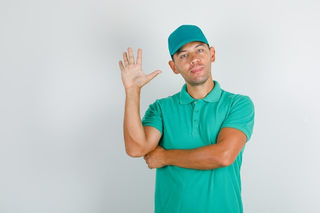 Powitanie człowieka dostawy z otwartą ręką w zielonej koszulce z czapką