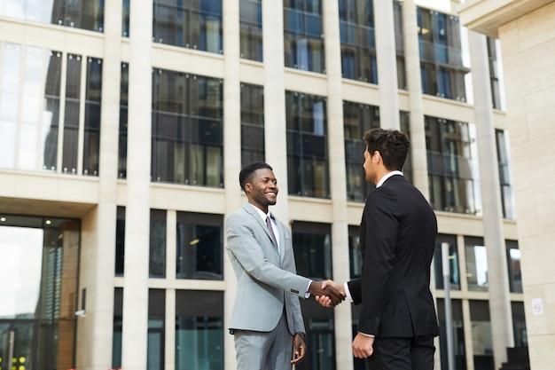 Powitanie dwóch biznesmenów na zewnątrz