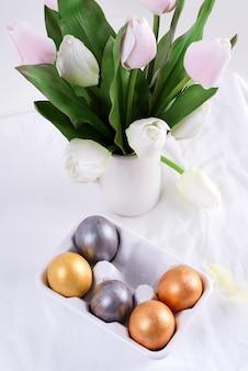 Powitanie kartka wielkanocna z ręcznie malowanymi jasnymi jajkami i bukietem świeżych kwiatów tulipanów