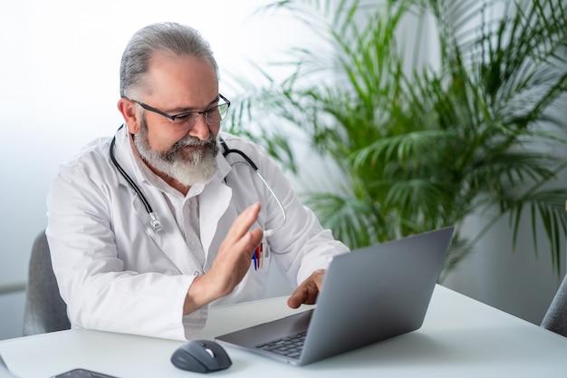 Powitanie lekarza podczas wideokonferencji w laptopie z koncepcją pracy telematycznej lub online pacjenta