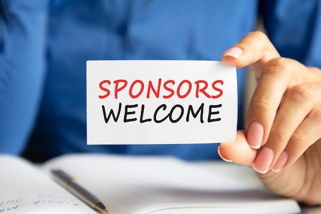 Powitanie sponsorów jest wypisane na białej wizytówce w kobiecej dłoni. niebieskie tło. koncepcja biznesowa i reklamowa