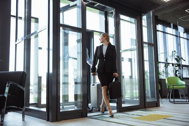 Powitanie. spotkanie młodych partnerów biznesowych po dotarciu do miejsca zakończenia podróży służbowej. mężczyzna i kobieta chodzenie na tle szklanej ściany nowoczesnego budynku. pojęcie biznesu, finansów, reklamy.