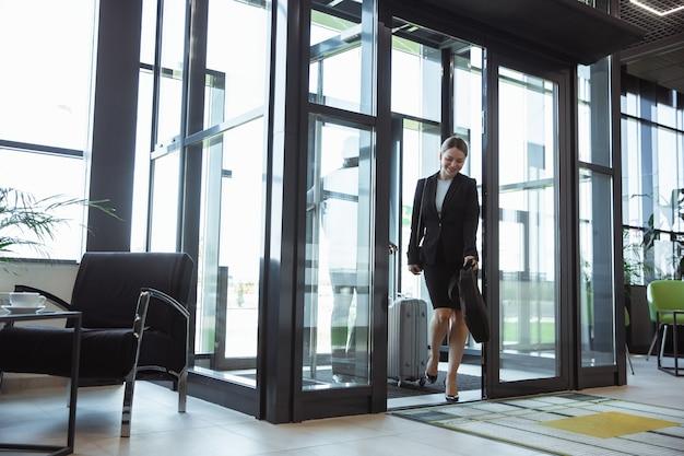 Powitanie. spotkanie młodych partnerów biznesowych po dotarciu do miejsca zakończenia podróży służbowej. mężczyzna i kobieta spaceru przed szklaną ścianą tle nowoczesnego budynku. pojęcie biznesu, finansów, reklamy.