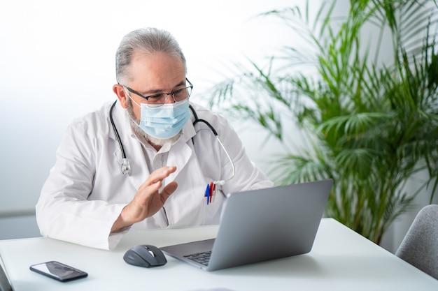 Powitanie starszego lekarza podczas wideokonferencji na laptopie z pacjentem