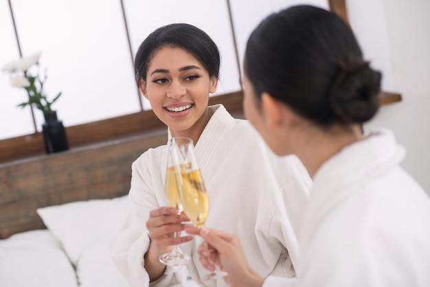 Powód do świętowania. ładne atrakcyjne kobiety uśmiechnięte, ciesząc się razem z szampanem