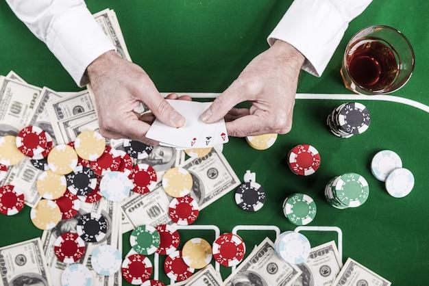 Powodzenia. widok z góry na mężczyznę trzymającego karty siedzącego przy stole pokerowym z mnóstwem żetonów i pieniędzy leżących na nim