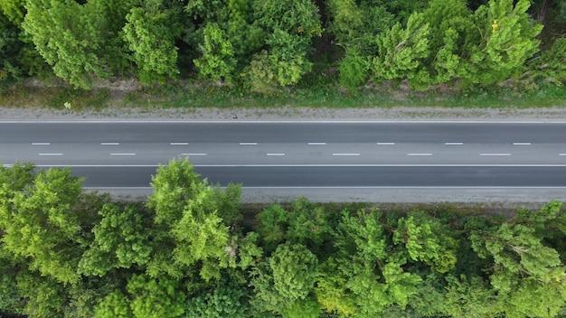 Powolny lot wysoko nad drogą między drzewami. ruch pojazdów asfaltowych.