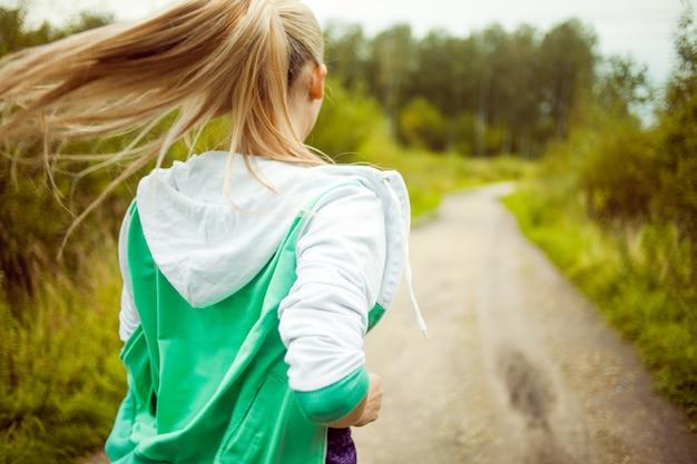 Powrót biegacz dziewcząt na drodze, poranny jogging