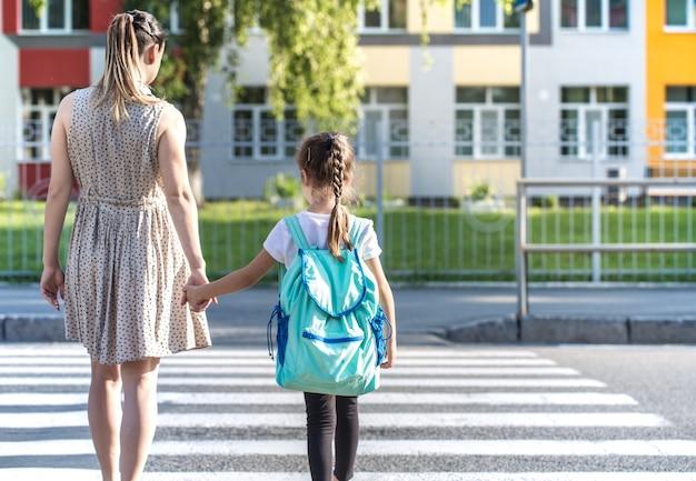 Powrót do koncepcji edukacji szkolnej z dziećmi dziewczynki, uczniów szkół podstawowych, niosąc plecaki idąc do klasy trzymając się za rękę razem spacerując