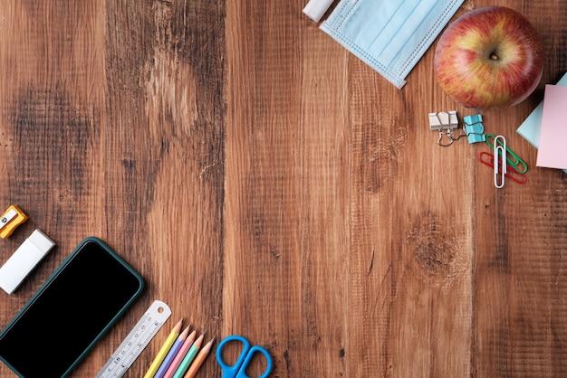 Powrót do koncepcji projektu ucznia szkoły, widok z góry papeterii na tle drewniany stół z miejsca kopiowania.