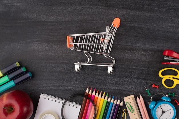 Powrót do koncepcji reklamy zakupów artykułów papierniczych w szkole. widok z góry na zdjęcie małego wózka w centrum jabłka i kolorowej papeterii izolowanej na tablicy z copyspace