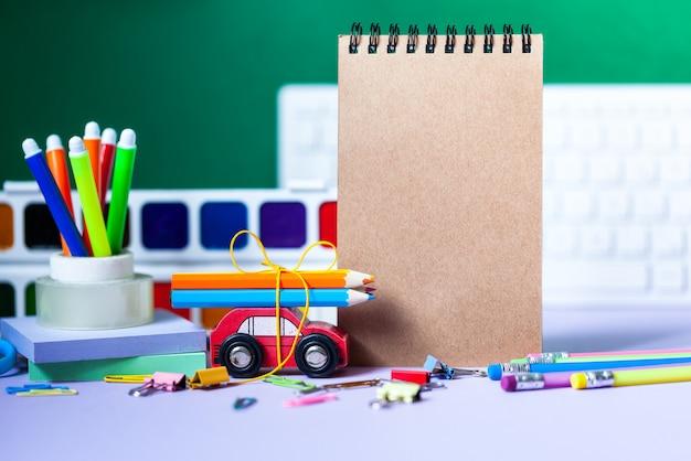 Powrót do koncepcji szkoły. artykuły szkolne i biurowe, kolorowe długopisy, ołówki, farby na zielono
