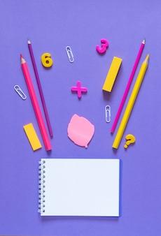 Powrót do koncepcji szkoły. artykuły szkolne i biurowe na stole biurowym. fioletowe tło.płaskie leżało z kopią przestrzeni.jesienne