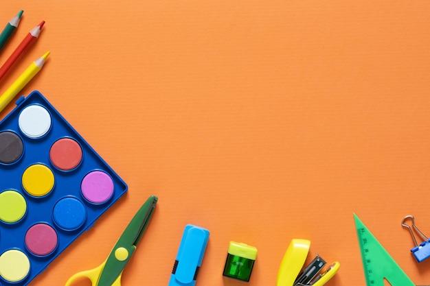 Powrót do koncepcji szkoły. artykuły szkolne i biurowe na stole biurowym. pomarańczowe tło. mieszkanie leżało z kopią przestrzeni. jesień