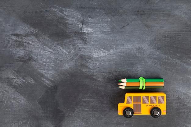 Powrót do koncepcji szkoły. autobus szkolny i ołówki na czarnym tle.