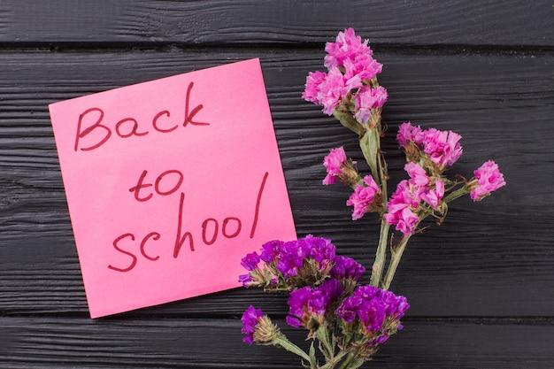 Powrót do koncepcji szkoły. bukiety różowe i fioletowe kwiaty na ciemnym drewnianym stole.