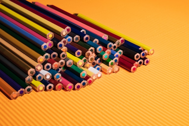 Powrót do koncepcji szkoły. colour ołówki na pomarańczowym tle.