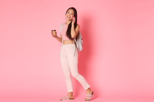 Powrót do koncepcji szkoły, edukacji i stylu życia. pełna długość pięknej azjatki z plecakiem, pije kawę i rozmawia przez telefon komórkowy, uśmiechając się nad różową ścianą