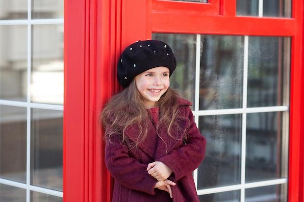 Powrót do koncepcji szkoły, jesień. mała wesoła dziewczyna stoi w pobliżu czerwonej budki telefonicznej w londynie w pięknym burgundowym płaszczu i bierze i uśmiecha się. anglia, zjednoczone królestwo. podróże po europie. edukacja.