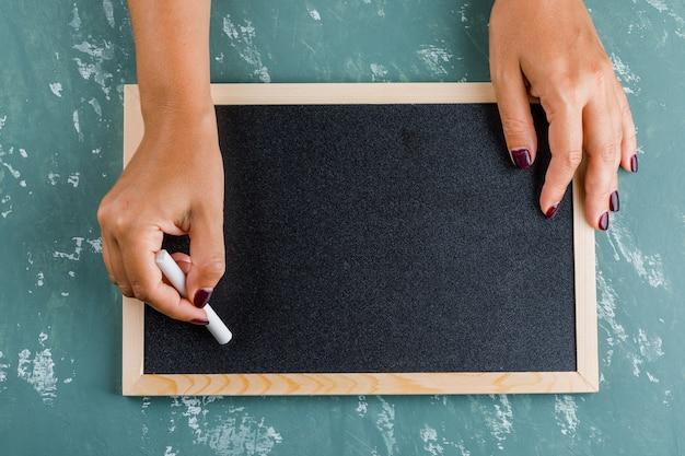 Powrót do koncepcji szkoły. kobieta pisze na tablicy kredą.
