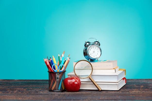 Powrót do koncepcji szkoły. książki, kolorowe kredki i zegar