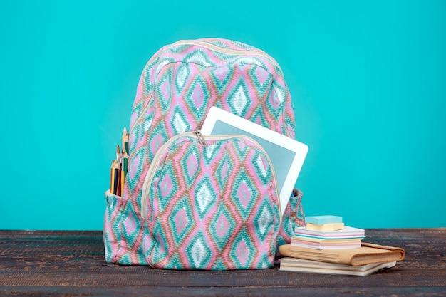 Powrót do koncepcji szkoły. książki, kolorowe ołówki i plecak
