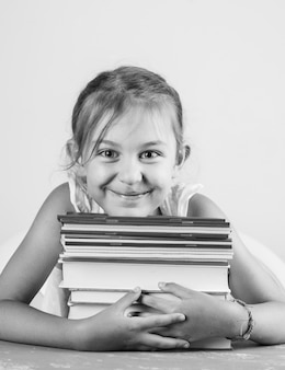 Powrót do koncepcji szkoły na tynk i widok z boku białej ściany. mała dziewczynka przytulanie zeszytów i książek.