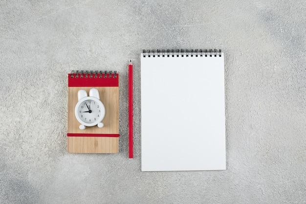 Powrót do koncepcji szkoły. notatnik, ołówek, budzik. leżał płasko, widok z góry, miejsce
