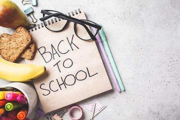 Powrót do koncepcji szkoły. notatnik, szkła, pióra i materiały przedmioty na szarym tle, odgórny widok.
