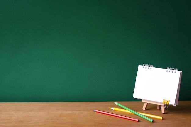 Powrót do koncepcji szkoły, otwarty notatnik na miniaturowej sztalugach i kilka kolorowych ołówków