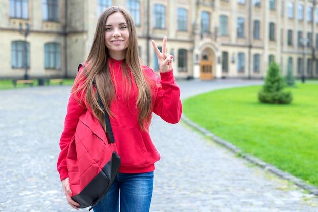 Powrót do koncepcji szkoły. portret jednego w jasnych dżinsach ubranie na co dzień młoda dama milenialsów dająca znak v stojącej w pobliżu drzwi budynku edukacyjnego